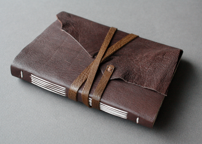 Longstitch binding with a leather strap